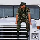 Person in army fatigues sitting on bus hood
